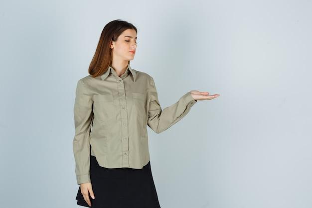 Giovane donna che guarda il palmo allargato in camicia, gonna e sembra concentrata, vista frontale.