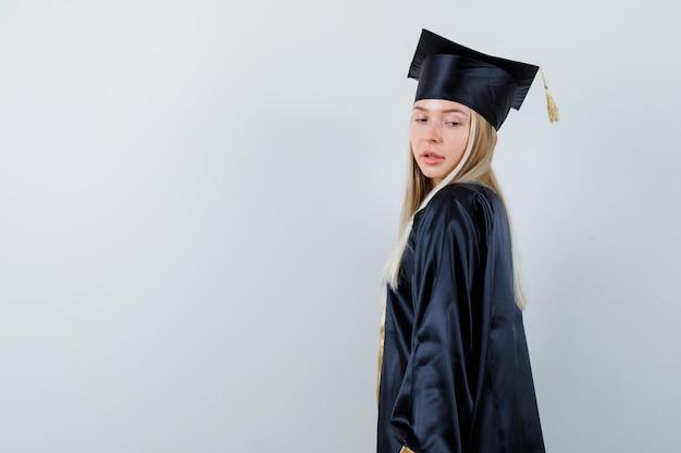 Giovane femmina che osserva sopra la sua spalla in uniforme laureata e che sembra seducente. .