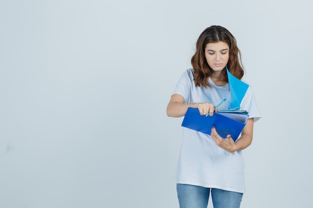 Young female looking over notes on folders in white t-shirt, jeans and looking focused , front view.