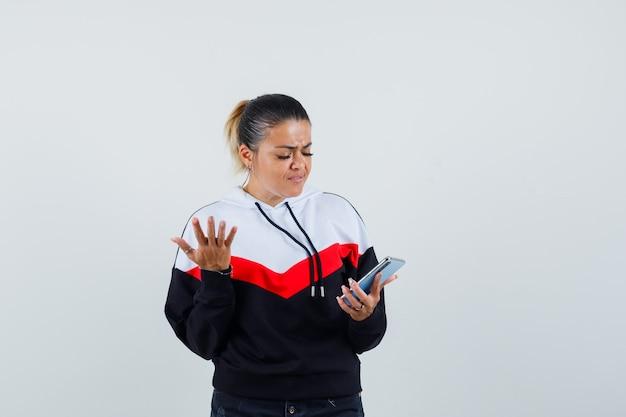 Молодая женщина ищет телефон, агрессивно поднимая руку в красочной толстовке и нервно глядя, вид спереди.