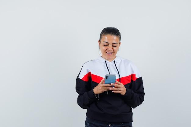 Молодая женщина смотрит фотографии на телефоне в красочной толстовке и выглядит довольной, вид спереди.