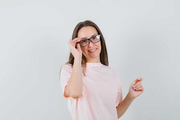 ピンクのtシャツを着て眼鏡をかけて陽気に見える若い女性。正面図。