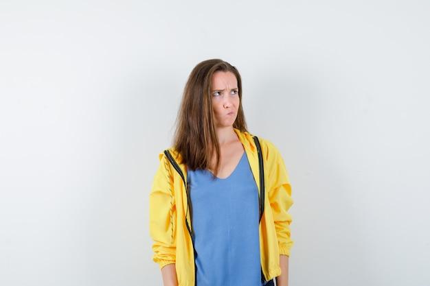 Giovane donna alzando lo sguardo, soffiandosi la guancia in maglietta, giacca e guardando pensierosa. vista frontale.