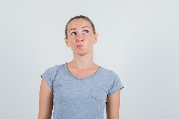 Молодая женщина смотрит вверх в серой футболке и смотрит задумчиво, вид спереди.