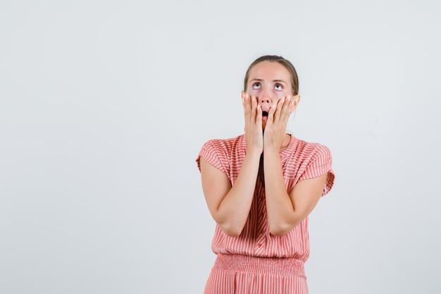Молодая женщина смотрит вверх руками на щеках в полосатом платье и выглядит испуганной, вид спереди.