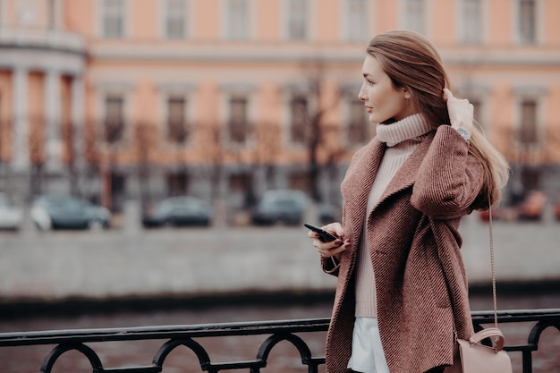 Young female looks aside with thoughtful expression, holds modern cell phone, waits for call