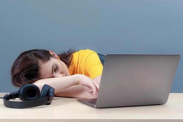 Молодая женщина, лежащая рядом с ноутбуком после слишком долгой работы, онлайн-работы или обучения