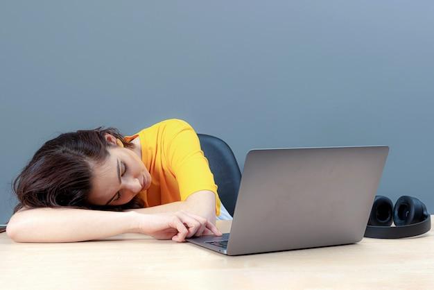 너무 오래, 온라인 작업 또는 학습 개념을 위해 일한 후 노트북 근처에 누워있는 젊은 여성