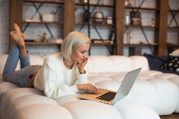 침대에 누워 있는 젊은 여성은 즐거운 미소로 온라인 쇼핑과 전자상거래를 위해 노트북 컴퓨터를 사용합니다