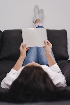 책을 읽고 벽에 누워 발을 가진 젊은 여성