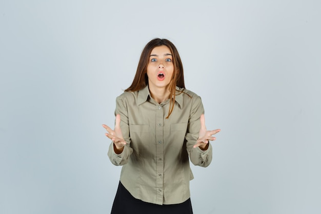 Young female making asking question gesture in shirt, skirt and looking shocked. front view.