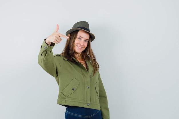 Giovane femmina che fa il segno della pistola del dito in giacca, pantaloni, cappello e che sembra fiducioso. vista frontale.