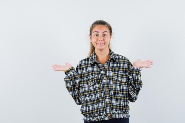Giovane femmina che fa il gesto del telaio in camicia controllata e guardando fiducioso, vista frontale.