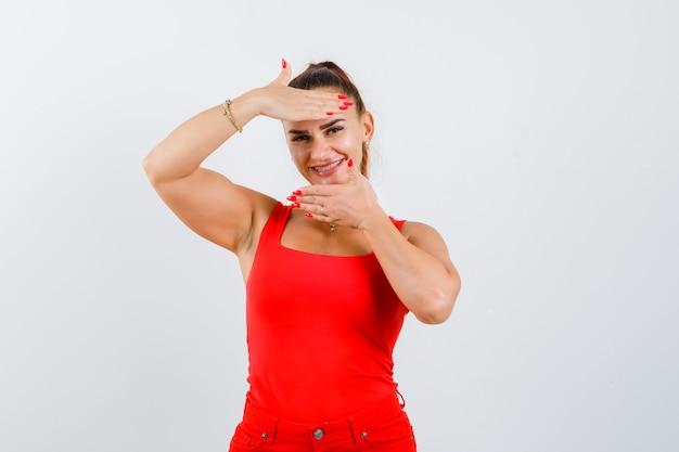 赤いタンクトップ、パンツ、魅力的な外観、正面図でフレームジェスチャーを作る若い女性。