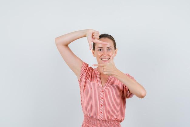 縞模様のドレスでフレームジェスチャーをし、嬉しそうに見える若い女性、正面図。