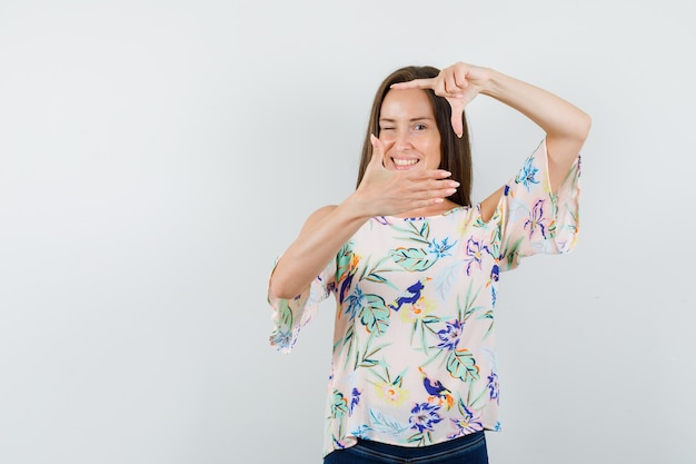 Giovane femmina che fa il gesto del telaio in camicia, jeans e guardando allegro, vista frontale.