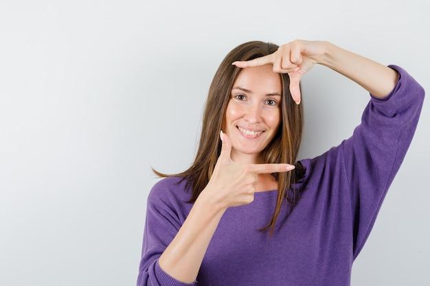 Giovane femmina che fa gesto del telaio in camicia viola e che sembra felice, vista frontale.