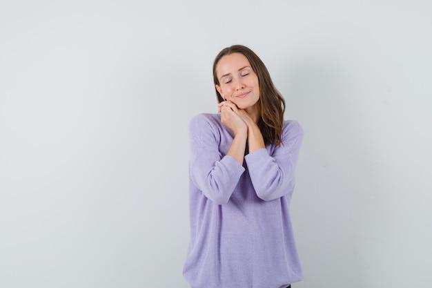 Молодая женщина делает жест подушкой в сиреневой блузке и выглядит сонной. передний план. свободное место для вашего текста
