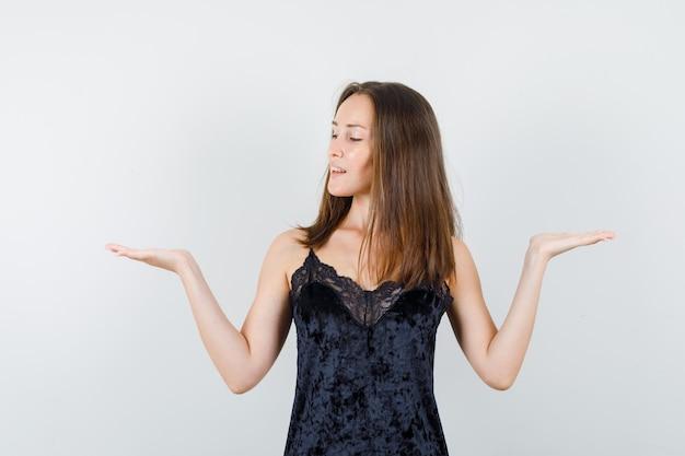 黒い一重項で体重計のジェスチャーをし、平和に見える若い女性