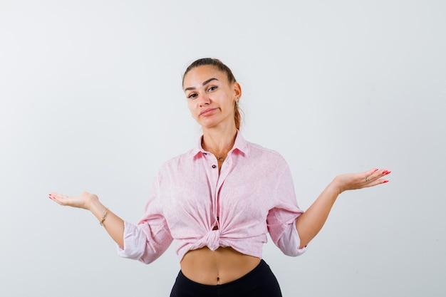 Молодая женщина делает жест весы в повседневной рубашке, штанах и выглядит нерешительно