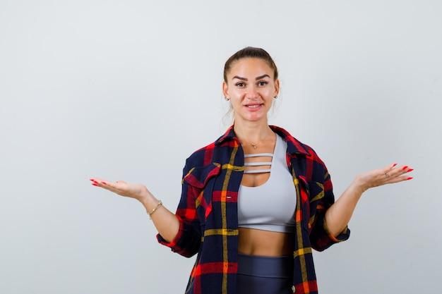 젊은 여성은 작물 상의, 체크무늬 셔츠, 바지를 입고 자신감을 갖고 앞모습을 보고 비늘 몸짓을 합니다.