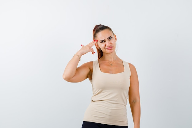 Young female making suicide gesture in beige tank top and looking hopeless , front view.