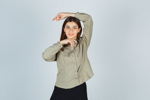 Giovane femmina che fa moda posa in camicia, gonna e sguardo seducente