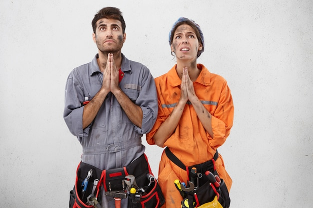 Young female and male plumbers keep hand as pray