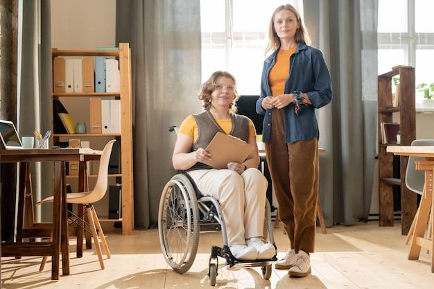 Молодая женщина-менеджер и ее коллега-инвалид стоят в центре офиса между рабочими местами у окна и полок с документами