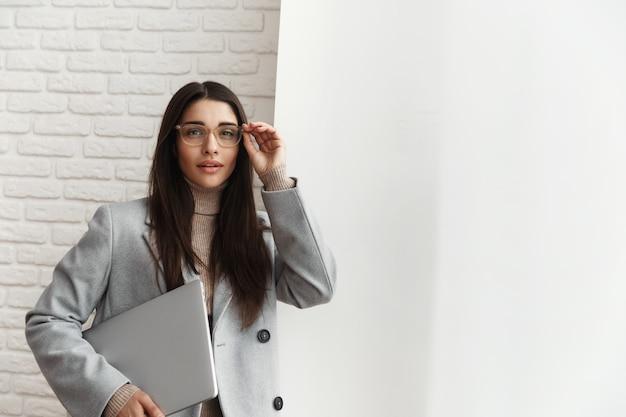 Молодая женщина-менеджер в очках, стоя возле окна офиса, держа в руке ноутбук.