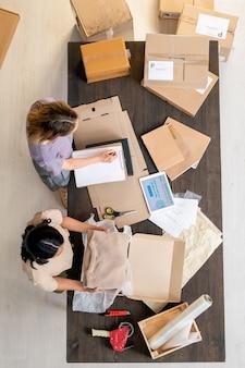 Молодая женщина-менеджер интернет-магазина упаковывает свернутый свитер в коробку, пока ее коллега составляет список пунктов по столу в офисе