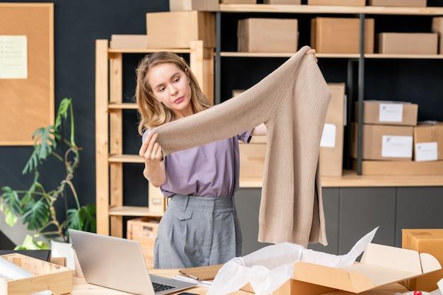 Молодая женщина-менеджер складского помещения интернет-магазина стоит у стола и смотрит на вязаный шерстяной свитер, прежде чем положить его в картонную коробку