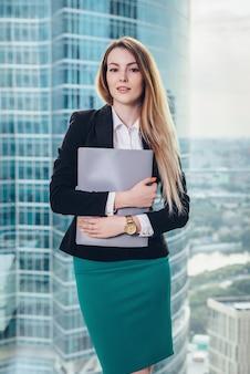 Молодая женщина-менеджер, стоя в офисе, держа в руках папку против окна с видом на деловой центр города.