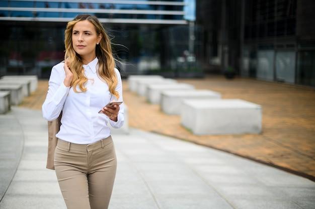 スマートフォンを使用しながら屋外を歩く若い女性マネージャー