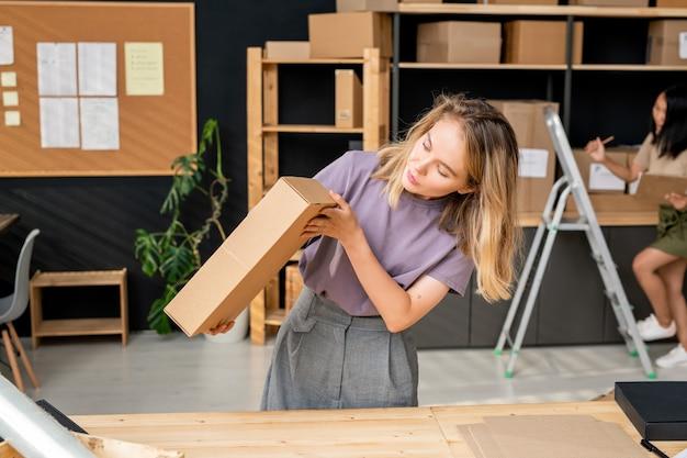 Молодая женщина-менеджер с длинными светлыми волосами проверяет качество упаковочной картонной коробки с заказом клиента во время работы в кладовой