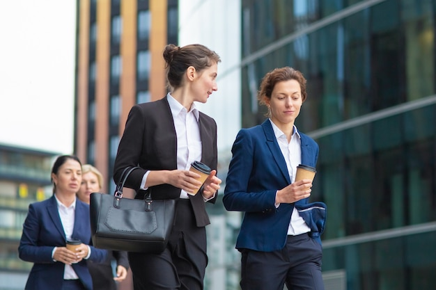 Young female managers with takeaway coffee mugs wearing office suits, walking together in city, talking, discussing project or chatting. medium shot. work break concept