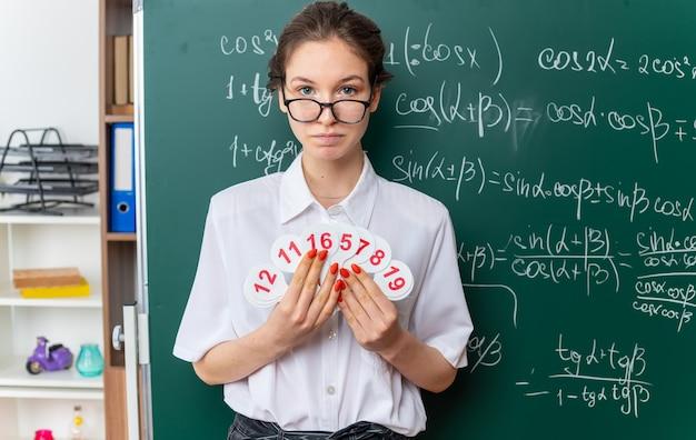 안경을 쓴 젊은 여성 수학 교사가 교실 앞을 바라보는 팬을 들고 칠판 앞에 서 있다