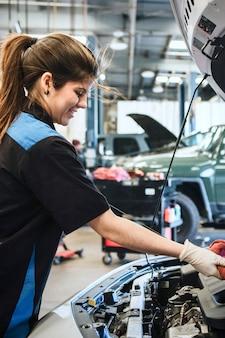 エンジンオイルレベルゲージを拭く若い女性整備士