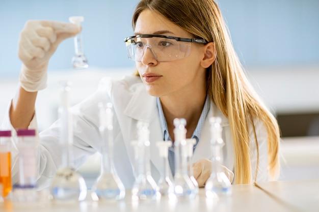 실험실에서 솔루션과 플라스크를보고 젊은 여성 의료 또는 과학 연구원