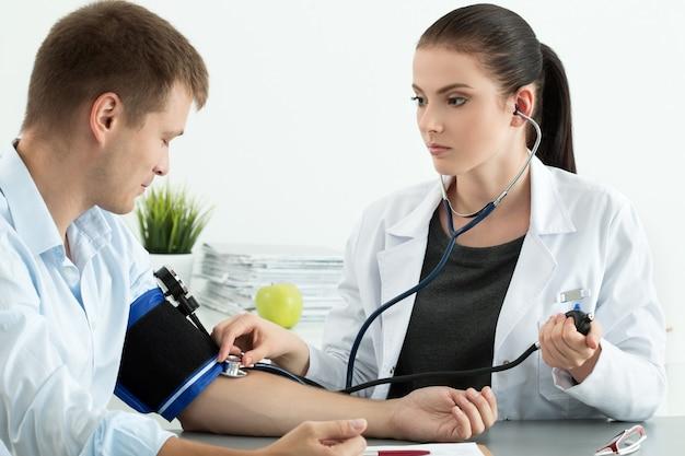 若い女性医学博士が患者に血圧を測定します。医療とヘルスケアの概念