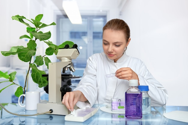Young female microscopist in white coat selects a tissue sample for microscopyspace