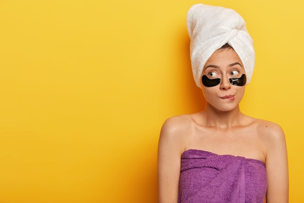 Young female model bites lips and looks thoughtfully away, wears towel after taking bath, applies pads for reducing wrinkles