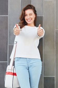 Young female model gesturing thumbs up sign