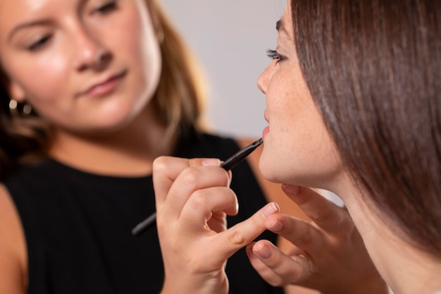 Young female model having her make up done by a professional artist