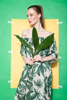 Молодая женщина-модель в стильном платье с цветочным орнаментом держит лист и смотрит в сторону, стоя на листе желтой бумаги на зеленом фоне летом