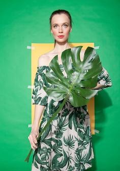 Молодая женщина-модель в стильном платье с цветочным орнаментом держит лист, стоя на листе желтой бумаги на зеленом фоне летом