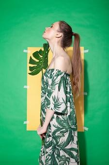 Молодая женщина-модель в стильном платье с цветочным орнаментом держит лист монстеры, стоя на листе желтой бумаги на зеленом фоне летом