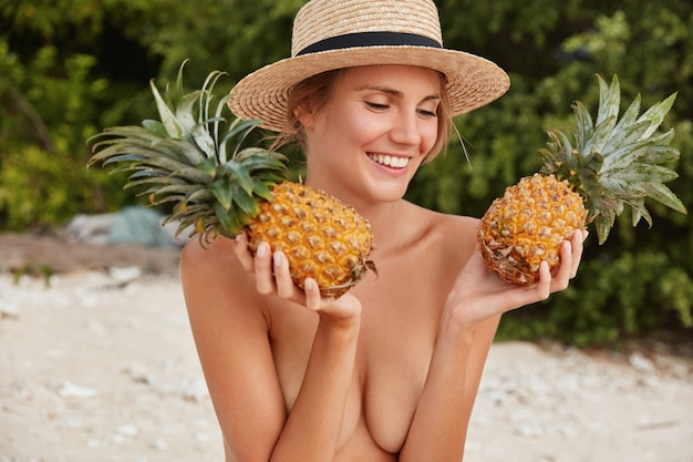 Young female model poses with two exotic pineapples