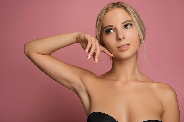 Young female model posing on pink background