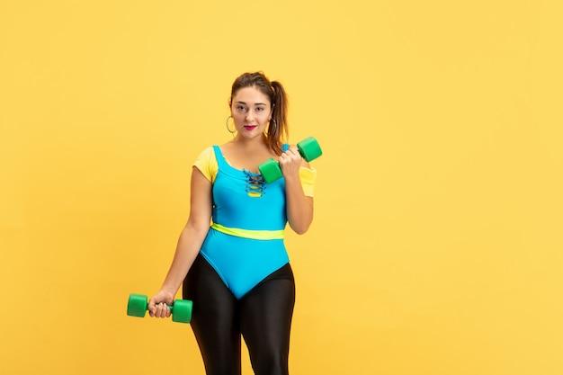 노란색 벽에 젊은 여성 모델 교육